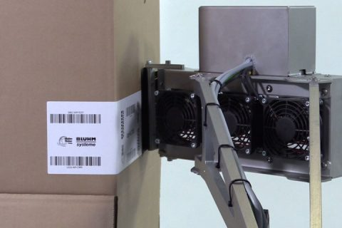 A label being applied to a cardboard
