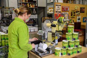 Operatrice inserisce lattina di caffè per l'etichettatura